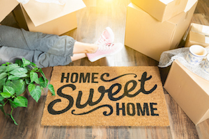 Woman with legs stretched out on a welcome mat with the words Home Sweet Home